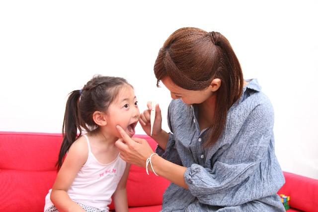 子供の歯を磨く女性
