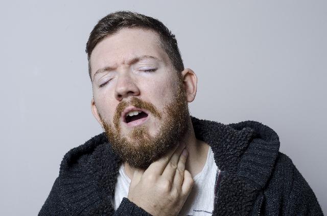喉を押さえる男性